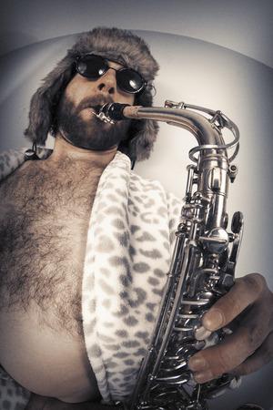 fisheye: Bearded hipster plays jazz saxophone in leopard print bathrobe taken with fisheye lens