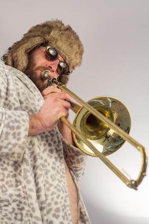 leopard print: Bearded hipster plays jazz trombone in leopard print bathrobe Stock Photo