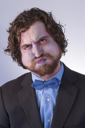 수염 난된 남자가 기대에 숨을 죽이고 푸른 색으로 변하고있다. 스톡 콘텐츠