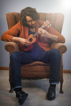 vintage chair: Bearded musician playing acoustic ukulele guitar in vintage chair