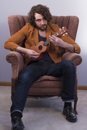 accoustic: Bearded musician playing acoustic ukulele guitar in vintage chair