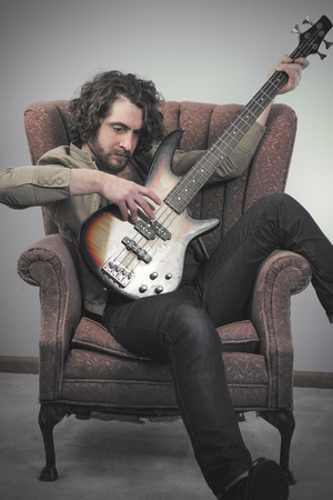 bass guitar: Bearded musician playing electric bass guitar in vintage chair Stock Photo