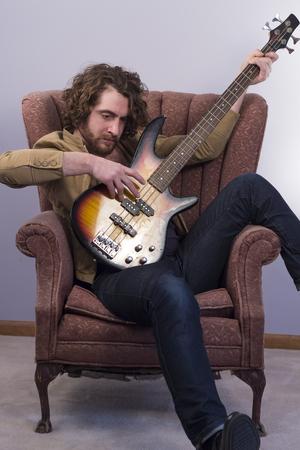 Bebaarde muzikant spelen elektrische basgitaar in uitstekende stoel