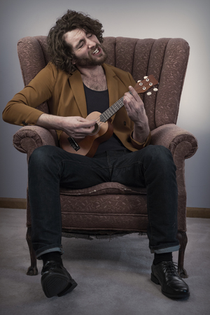Bearded musician playing acoustic ukulele guitar in vintage chair