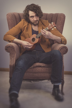 soprano: Bearded musician playing acoustic ukulele guitar in vintage chair