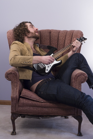 Bearded musician playing electric ukulele guitar in vintage chair