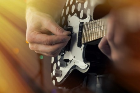 ukelele: Closeup shirtless male musician playing tenor electric ukulele