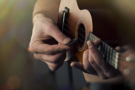 accoustic: Closeup shirtless male musician playing soprano ukulele