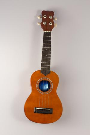 accoustic: Little wooden soprano hawaiian ukulele hanging on wall