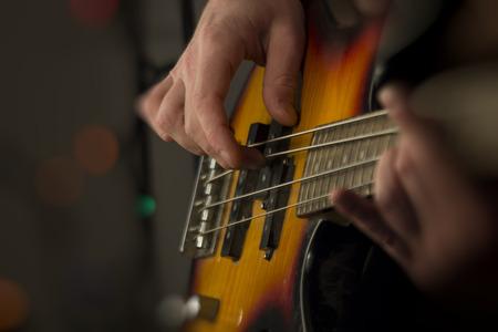 Close-up mannelijke muzikant speelt elektrische basgitaar