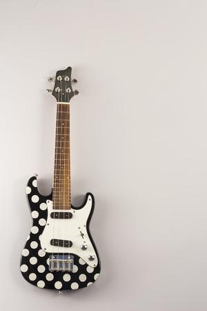 frets: Hanging tenor electric ukulele with polka dots Stock Photo