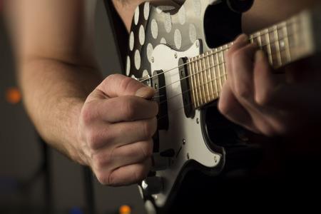 the tenor: Closeup shirtless male musician playing tenor electric ukulele