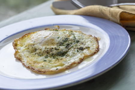 runny: Fried runny egg over easy with salt pepper and parsley Stock Photo