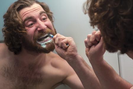 adult brushing teeth: Silly bearded man brushing teeth in bathroom mirror