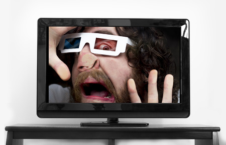 scared man: Silly bearded man wearing 3D glasses stuck inside TV screen Stock Photo