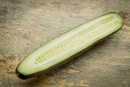 Cucumber sliced lengthwise with seeds on grungy wooden table