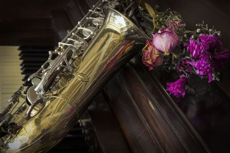 accoustic: Old and worn Jazz saxophone and piano with dried roses Stock Photo