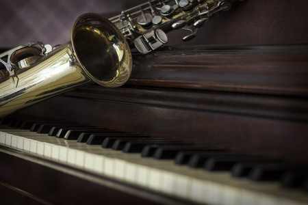 jazz musician: Old and worn Jazz saxophone and piano musical background Stock Photo