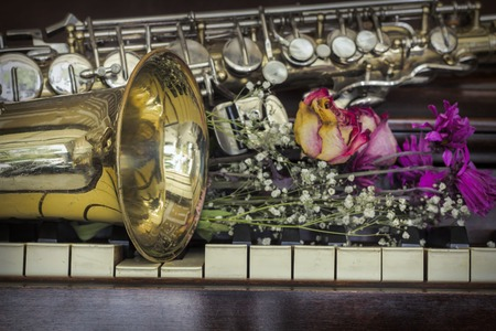 Old and worn Jazz saxophone and piano with dried roses Stock Photo