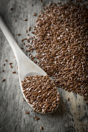 flax seed: Close up flax seed on rustic worn wooden table surface Stock Photo