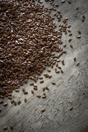 common flax: Close up flax seed on rustic worn wooden table surface Stock Photo