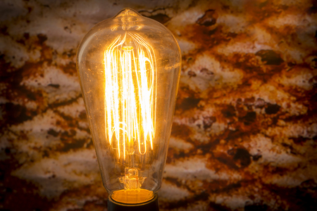 metal filament: Decorative antique edison style filament light bulb with rusty metal background Stock Photo