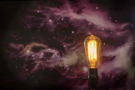 starscape: Decorative antique edison style filament light bulb with starscape background