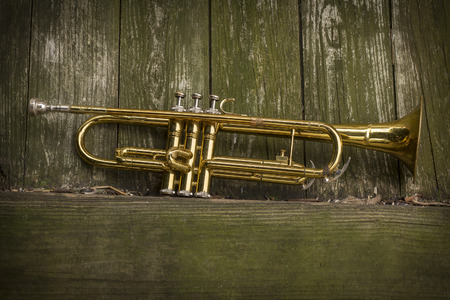 pealing: Old worn trumpet stands alone against a grungy wall Stock Photo