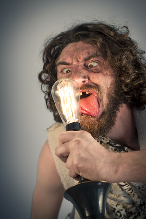 homo erectus: Silly realistic caveman dumbfounded by confusing edison lightbulb
