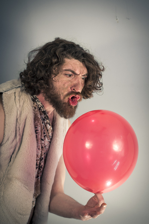 homo erectus: Silly caveman grunts at confusing red birthday balloon
