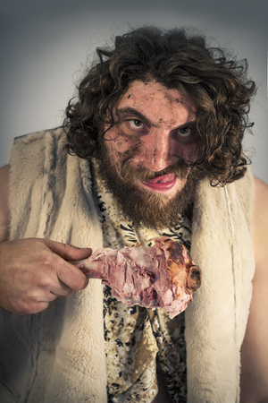 homo erectus: Silly hungry cave man eating ham on the bone Stock Photo