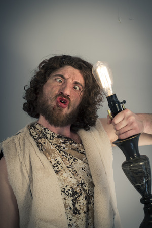 Silly realistic caveman dumbfounded by confusing edison lightbulb