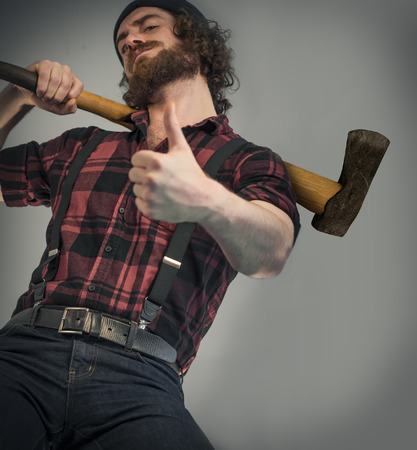 Silly hipster lumberjack gives thumbs up sign while holding axe