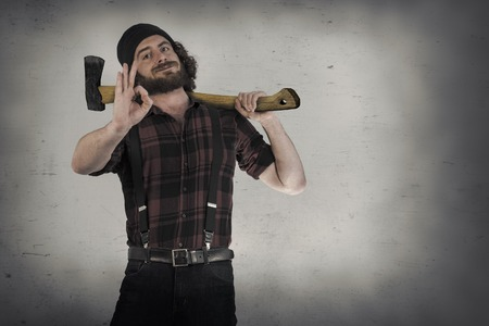 Silly hipster lumberjack gives okay sign while holding axe Stock Photo