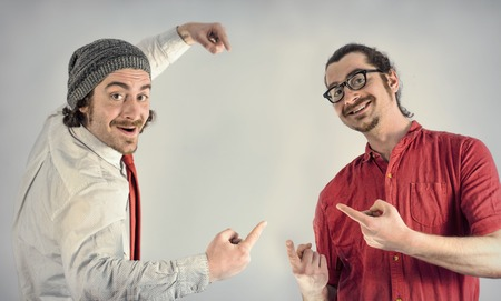together with long tie: Twin adult men with beards making hand gestures and pointing