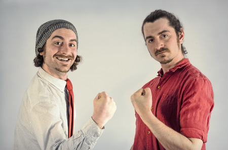 together with long tie: Twin adult men with beards fist pump after victory