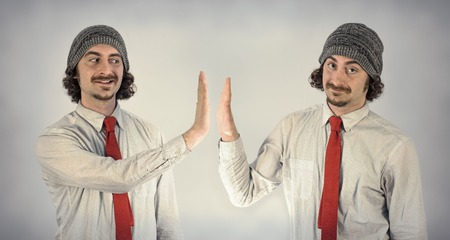 together with long tie: Twin adult men with beards high five eachother