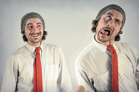 together with long tie: Twin adult men with beards making silly facial expressions