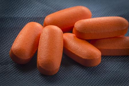 pain killer: Macro close up orange pain killer pills on blue background
