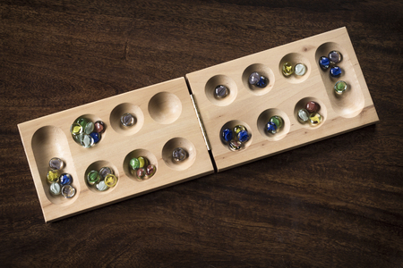 Traditional Mancala boardgame with glass pieces on wooden table Stockfoto
