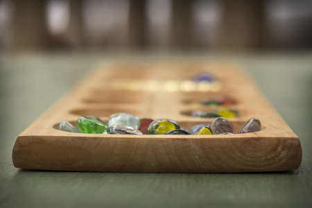 mind games: Traditional Mancala boardgame with glass pieces on wooden table Stock Photo
