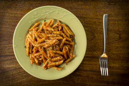 Penne alla vodka in rustic kitchen setting on green plate Stock Photo