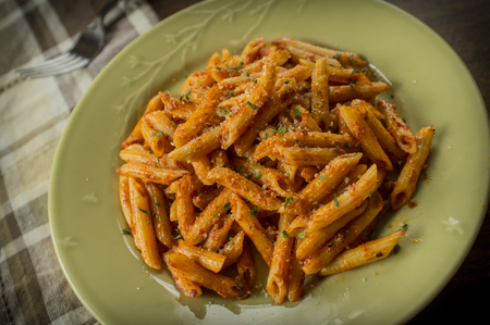 Penne alla vodka in rustic kitchen setting on green plate Stock Photo - 56519252