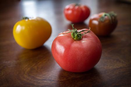 木製のテーブルにカラフルなジューシーな家宝または遺産トマト