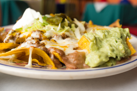 shredded cheese: Mexican beef nachos with sour cream guacamole and melted shredded cheese