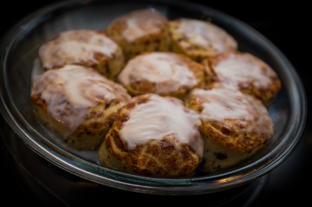 several breads: Closeup of several cinnamon buns on display on black table top