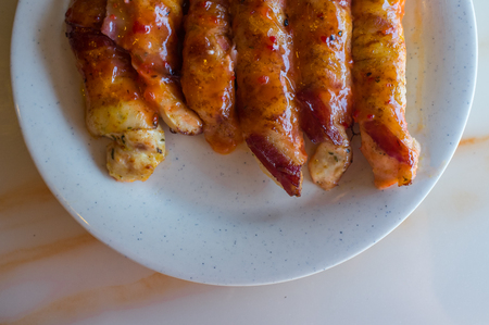 tenders: Bacon wrapped chicken tenders in honey glaze arranged on plate