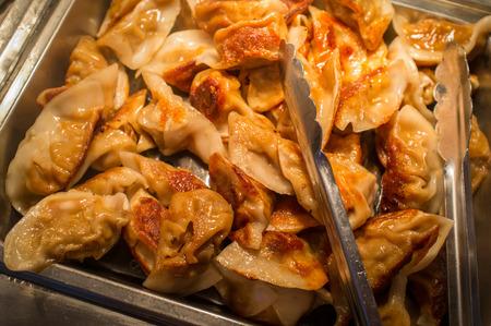 Buffet tray of fried Asian potsticker pork dumplings Stock Photo