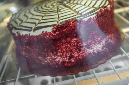 display case: Red velvet cake with chocolate icing pattern in bakery display case Stock Photo