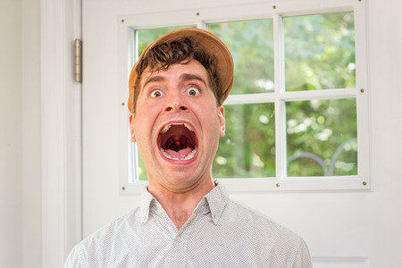 newsboy cap: Young handsome curly haired man wearing newsboy hat screaming at the top of his lungs Stock Photo